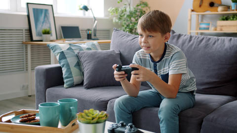 Smiling little boy playing video game at home alone having fun with cool device Live Action