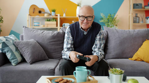 Senior man playing video game at home sitting on sofa at home enjoying leisure Live Action
