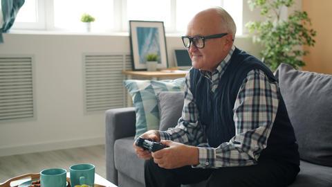 Joyful senior man playing video game alone entertaining at home enjoying gaming Live Action