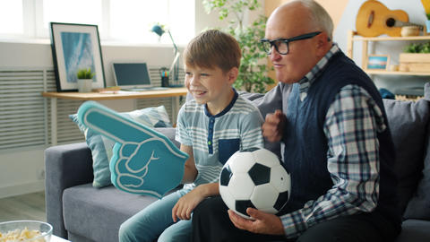Caring grandad and happy boy watching football on TV holding foam hand and ball Live Action