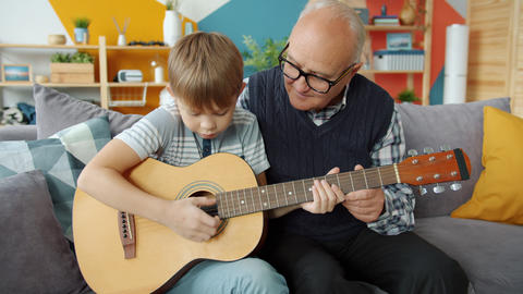 Old man teaching talented little grandson to play the guitar in apartment Live Action