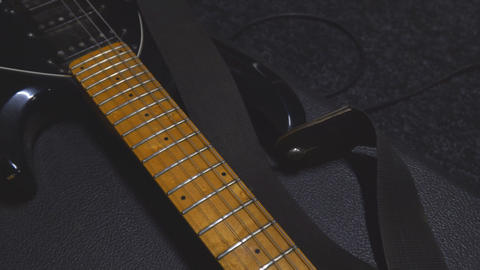 A black guitar with a light wood neck rests on the case Live Action