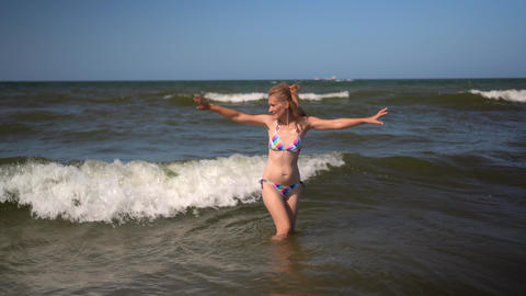 Young, fit and attractive girl catch sea waves in colorful bikini. Pretty woman Live Action