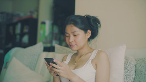 Portrait of Young Thai Woman that chilling out with smartphone on sofa Live Action