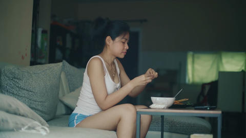 Young Thai Woman is eating sticky rice with sauce at home Live Action