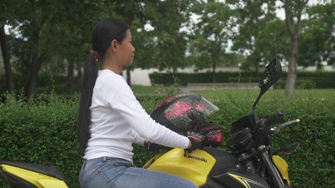 SAMUT PRAKAN, THAILAND - AUGUST 24, 2019: Thai Woman sitting on yellow motorcycle Kawasaki z650 and Live Action