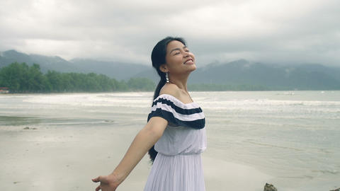 Pretty Asian Girl in dress enjoying fresh air at sea Live Action