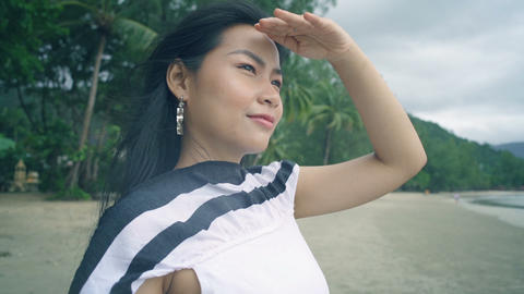 Portrait of Young Asian Woman at beach is looking on the sea Live Action