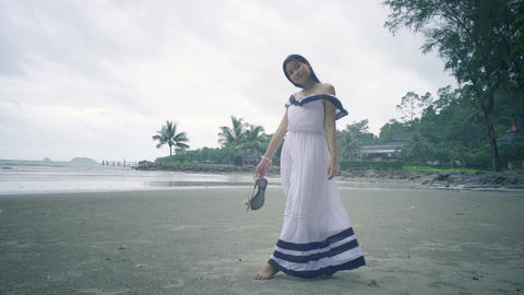 Barefooted Thai Girl at beach holding her shoes Live Action