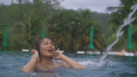 Young Asian Woman emerging from under water in a tropical swimming pool Live Action