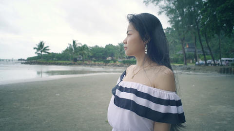 Portrait of Young Asian Woman at beach during raining Live Action