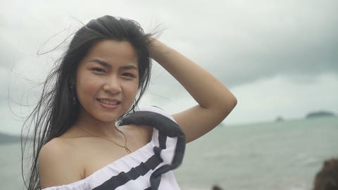 Portrait of smiling Thai Girl with long hair and sea on background Live Action