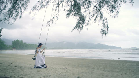 Young Woman in white dress swinging on a swing at beach Live Action