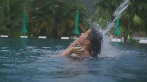 Young Asian Woman standing under water jet in a swimming pool Live Action