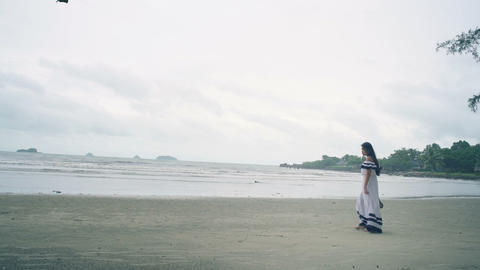 Young Woman in white dress walking at beach Live Action