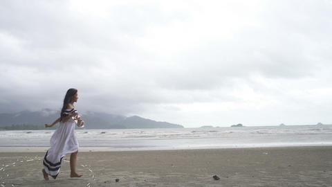 Thai Girl runs at beach with drawn footprints Live Action