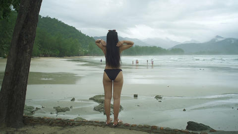 Young Thai Woman in bikini looking at tropical beach Live Action