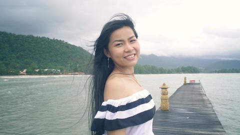 Portrait of smiling Thai Woman on pier Live Action
