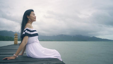 Young Asian Woman with long hair sitting on wooden pier Live Action