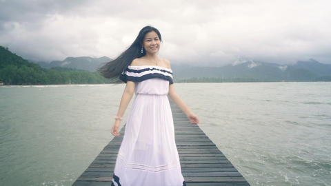 Pretty Thai Girl with long hair on wooden pier turning to camera Live Action