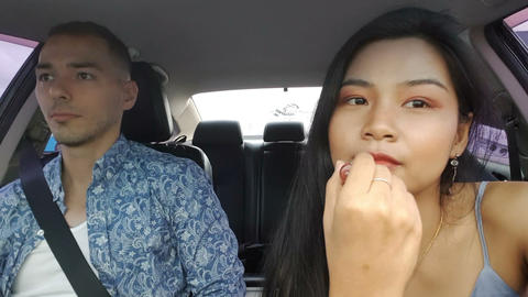 Young Asian Woman paints her lips with lipstick in a car Live Action