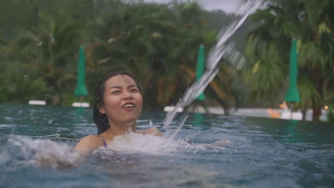 Thai Girl enjoying her vacation in a swimming pool Live Action