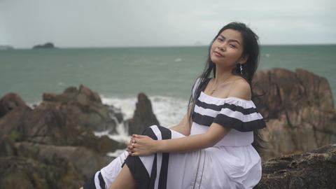 Happy Young Asian Woman sitting on rocks near sea Live Action