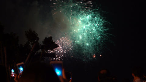 Crowd of people with smartphones watching fireworks Live Action