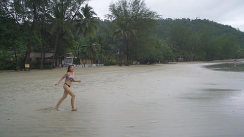 Young Thai Woman running at tropical beach Live Action