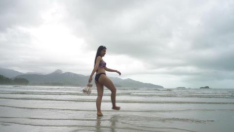 Young Woman in bikini kicks water at beach Live Action
