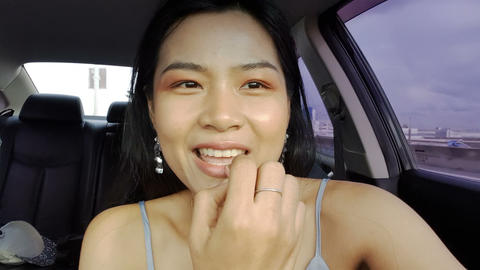 Thai girl doing makeup in a car Live Action
