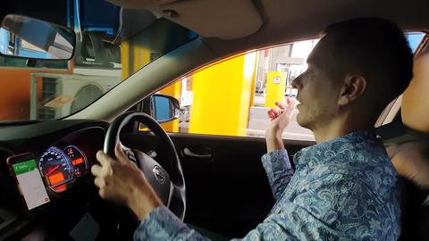 Man driving a car on Bang Na expressway, taking card and paying cash Live Action
