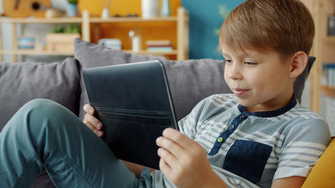 Slow motion of smiling child holding tablet watching video indoors in apartment Live Action