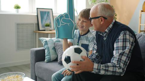 Cheerful family grandfather and grandson watching soccer on TV cheering Live Action