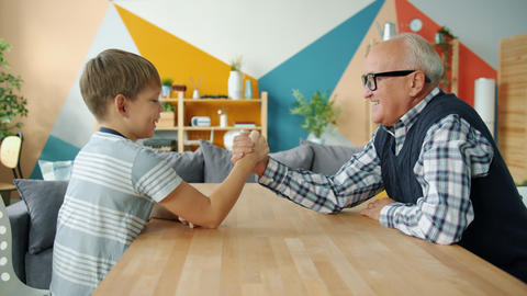 Caring grandfather teaching boy to wrestle having fun doing sports at home Live Action