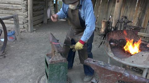 Blacksmith hammering red hot steel on anvil 4K Footage