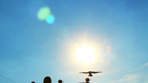 Flying aircraft at daytime silhouette through sun, landing light Footage