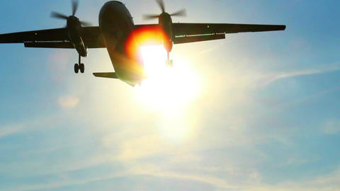 Airliner flies through sun rays at daytime, landing plane Footage