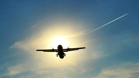 Airplane landing silhouette through sun rays, daytime, blue sky Footage