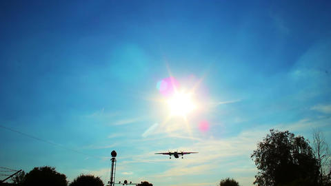 Large passenger airliner landing flying through sun rays Footage