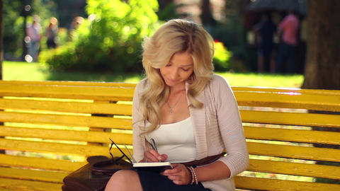 Young adult woman writes notes in notebook sitting bench park Footage