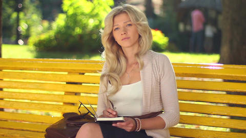 Young woman sitting on bench thinking writing notes smiling park Footage