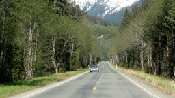 Car driving on Alaskan forest road towards camera HD 7098 Live Action