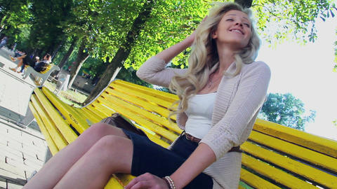 Enjoying smiling young beautiful young female in park bench Footage