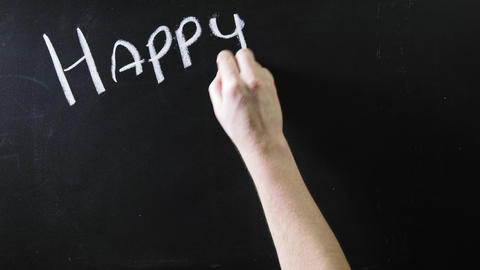 "The word ""happy new year"" written on a black chalkboard. The sign is written on Live Action"
