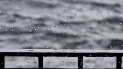 Raindrops on a window pane. Severe sea outside the window. Light wave on the surface of the sea. The Live Action