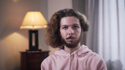 Face of young Caucasian man with long curly hair turning head and showing part Live Action