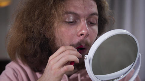 Close-up portrait of Caucasian intersex person looking at mirror and doing Live Action