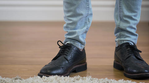 Male Caucasian feet in jeans and broggi shoes coming into shot, stopping, and Live Action