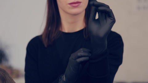 Makeup artist woman puts on rubber gloves before the procedure in a beauty salon Live Action